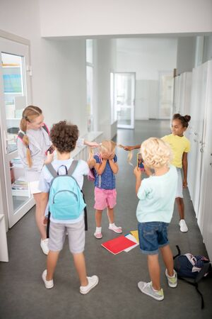 Bullying younger girl. Older pupils bullying poor younger girl while pilling her hair near lockers