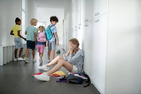 Girl crying. Schoolgirl sitting on the floor near lockers and crying because of bullying