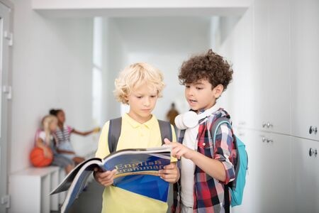 Repeating English grammar. Two boys holding book and repeating English grammar before lesson starts