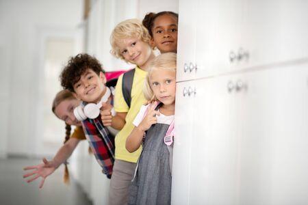 Cheerful children. Cheerful friendly and happy children standing near lockers while enjoying school break