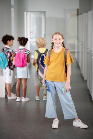 Stylish schoolgirl. Stylish schoolgirl holding penny board and smartphone while standing near lockers