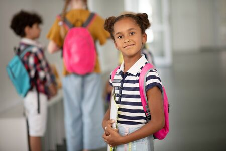 Girl with backpack. Dark-skinned girl wearing pink backpack feeling excited before lesson
