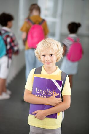 Schoolboy with book. Blonde-haired schoolboy holding English grammar book while walking to lesson