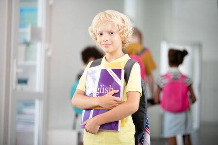 Dark-eyed boy. Dark-eyed handsome schoolboy wearing bright t-shirt walking to classroom
