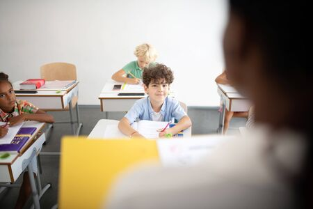 Looking at teacher. Curly dark-haired boy looking at teacher during the lesson at primary school
