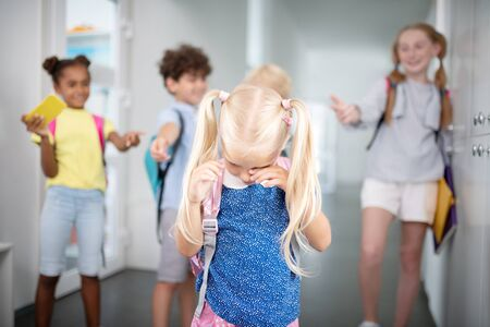 Little girl crying. Blonde-haired little girl crying while feeling offended by classmates