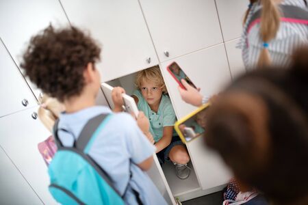 Bullying poor boy. Rude children bullying poor boy sitting in the locker and making photo of him