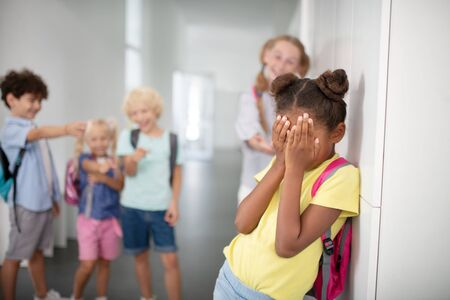 Girl closing face. Dark-skinned girl closing her face while suffering from bullying and feeling frustrated
