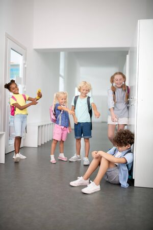 Bullying boy. Curly boy sitting on the floor while suffering from bullying by his classmates Stock Photo