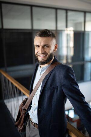 Cheerful businessman. Cheerful bearded businessman standing near stairs and enjoying little break Stok Fotoğraf