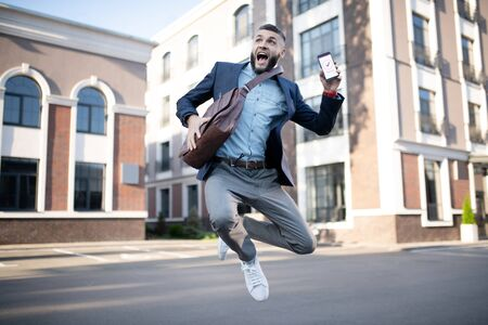 Handsome man jumping. Handsome man jumping after reading approving message from successful company Stockfoto