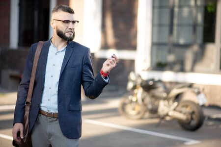 Holding car keys. Handsome bearded businessman holding his car keys while walking in the morning Foto de archivo - 129835911