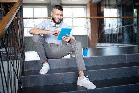Reading online news. Handsome man wearing white sneakers reading online news after drinking coffee