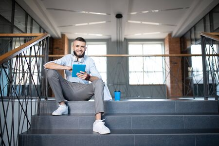 Sitting on stairs. Handsome smiling office worker sitting on stairs and using tablet while having break