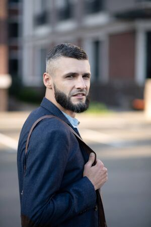 Successful businessman. Successful handsome bearded businessman wearing dark jacket standing outside