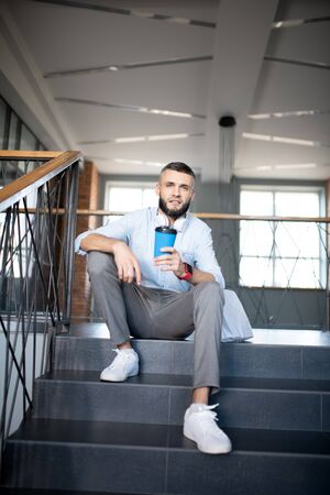 Drinking takeaway coffee. Handsome bearded office worker sitting on stairs and drinking takeaway coffee