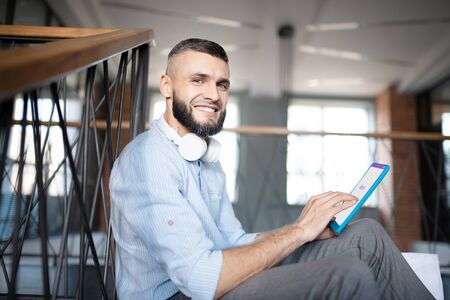 Holding little tablet. Bearded handsome young man with earphones on neck holding little tablet Stok Fotoğraf