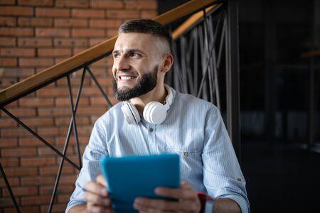 Smiling man. Smiling dark-eyed handsome man holding little tablet while having little break Stok Fotoğraf