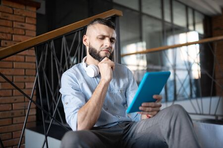 Reading e-mail. Bearded businessman wearing grey trousers reading e-mail and feeling thoughtful