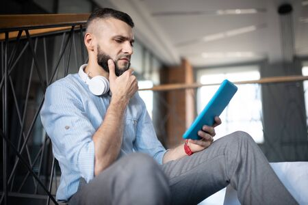Man feeling concerned. Bearded man with earphones on neck feeling concerned while reading financial news