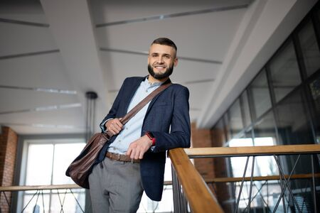 Beaming office worker. Beaming handsome young office worker wearing smart watch standing near stairs