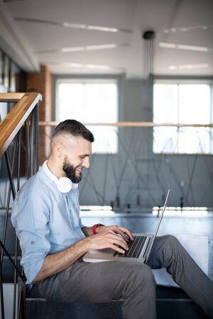 Freelancer working. Smiling successful freelancer feeling joyful while sitting on stairs and working