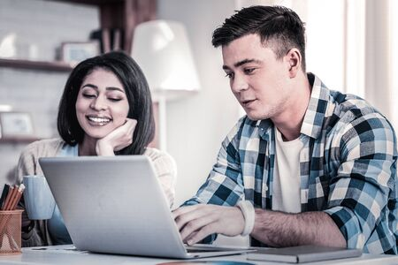 Caring young girlfriend. Hairy man in blue shirt busy with his computer while his smiling girlfriend sitting nearby