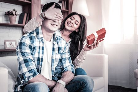 Carrying present. Long-haired smiling woman holding beautifully decorated box and showing it to her boyfriend Stok Fotoğraf