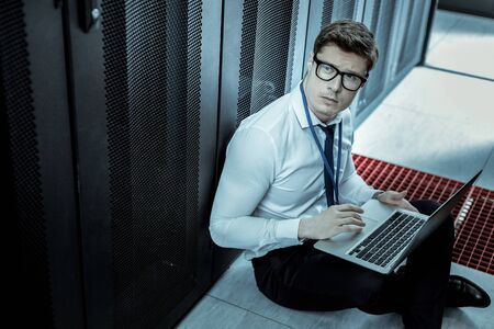 I have found something .Young detective with a laptop looking involved while analyzing internet security Banco de Imagens