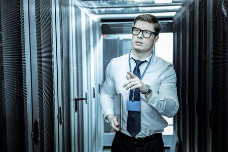 Drukke dag. Professioneel in een blauw shirt die op kantoor werkt terwijl hij onderzoek doet op het werk