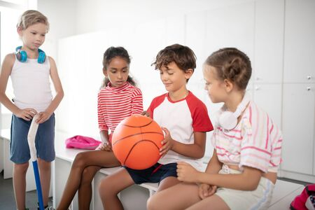 Excited before playing. Cute good-looking children feeling excited before playing basketball at PE class Stok Fotoğraf