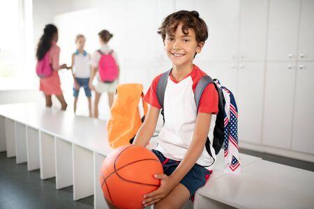 Boy holding ball. Dark-haired handsome schoolboy wearing backpack holding basketball ball Stok Fotoğraf