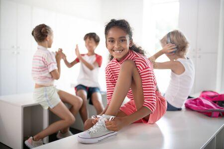 Happy girl. Cheerful dark-skinned girl feeling happy after PE class while sitting in locker room Stok Fotoğraf