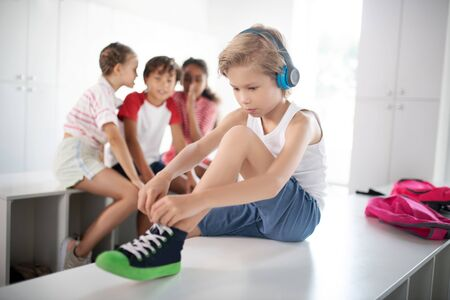 Boy lacing sneakers. Blonde boy wearing earphones lacing sneakers while classmates gossiping