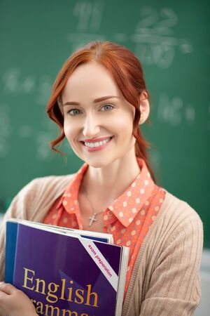 Teacher holding book. Cheerful English teacher holding book while standing near blackboard