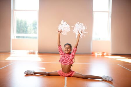 Doing leg split. Dark-skinned little cheerleader smiling while doing leg split while practicing Reklamní fotografie