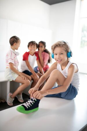 Listening to music. Cheerful blonde-haired boy listening to music while lacing sneakers