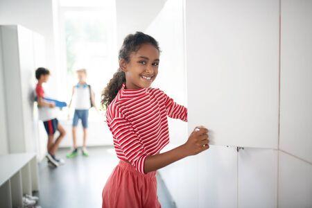 Standing near locker. Smiling dark-skinned girl wearing striped shirt standing near locker at school