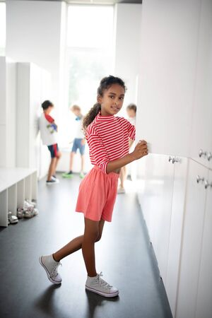 Wearing pink clothing. Curly dark-skinned girl wearing pink clothing standing near locker at school Stok Fotoğraf