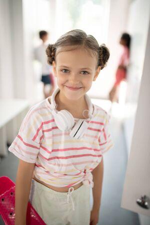 Girl feeling good. Cheerful dark-eyed girl wearing earphones on neck feeling good before PE class