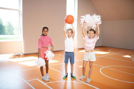 Little cute cheerleaders. Little cute cheerleaders standing near classmate with ball in the sports hall