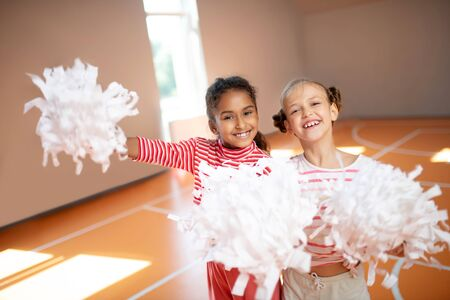 Best friends smiling. Best friends smiling while practicing cheerleading together at school