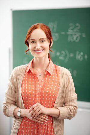 Beaming teacher. Red-haired beaming teacher smiling before the start of new school year