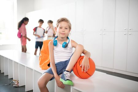 Ready for basketball. Blonde-haired schoolboy ready for playing basketball at physical training lesson