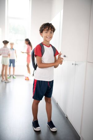 Wearing sport clothing. Dark-haired cheerful handsome boy wearing sport clothing standing near locker