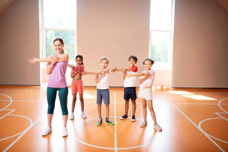 Stretching arms. PE teacher and children stretching arms before starting physical training all together