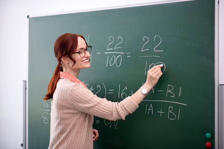 Explaining new topic. Smiling math teacher explaining new topic to her pupils near blackboard