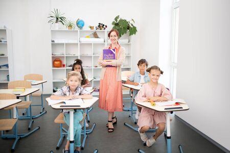 Pupils at desks. Four diligent pupils sitting at the desks near teacher before starting English class