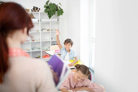 Luisteren naar schooljongen. Roodharige leraar luisteren naar slimme schooljongen die vraag beantwoordt