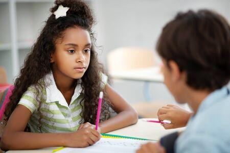 Listening to classmate. Cute dark-eyed girl listening to classmate while discussing test at the lesson